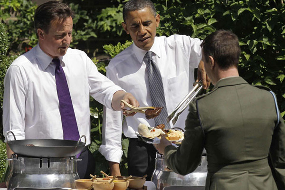 Prime Minister David Cameron and US President Barack Obama serve food to a serviceman during a barbecue in the garden of 10 Downing Street