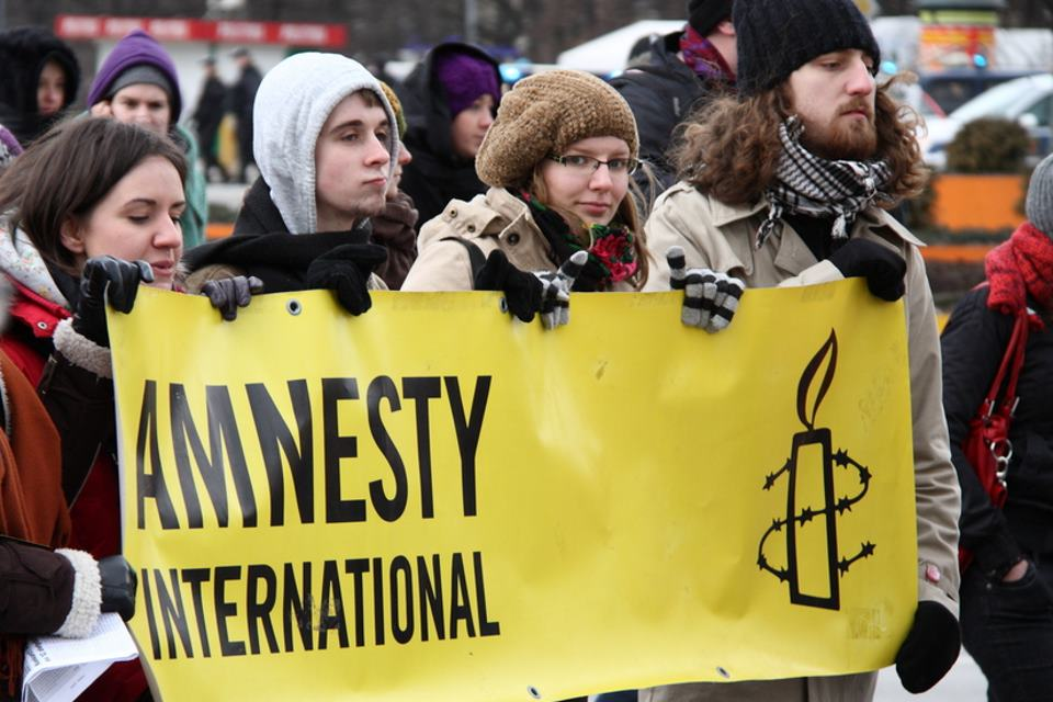 Amnesty International banner and supporters.