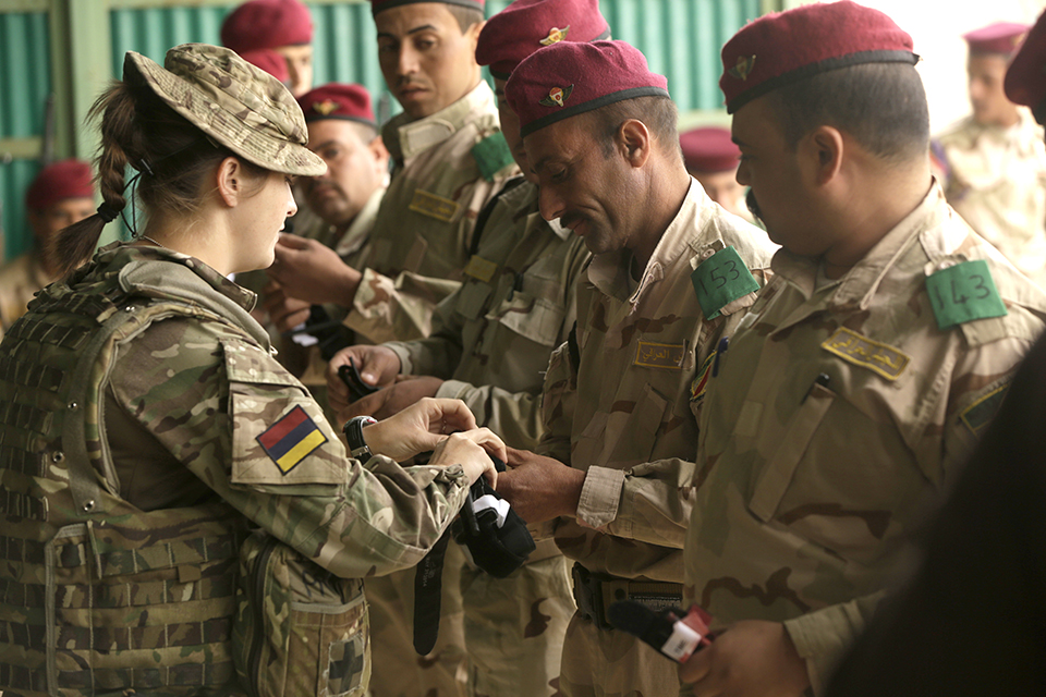 A British soldier with the Royal Army Medical Corps helps an Iraqi soldier prepare a tourniquet during a skills evaluation. Combined Joint Task Force - Operation Inherent Resolve Copyright.
