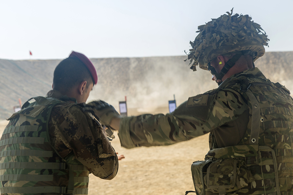 A British soldier helps an Iraqi soldier adjust his stance. Combined Joint Task Force - Operation Inherent Resolve Copyright.
