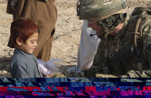 Lieutenant Ben Brading, A Company, 1st Battalion The Yorkshire Regiment, gives an Afghan child a gift for Eid