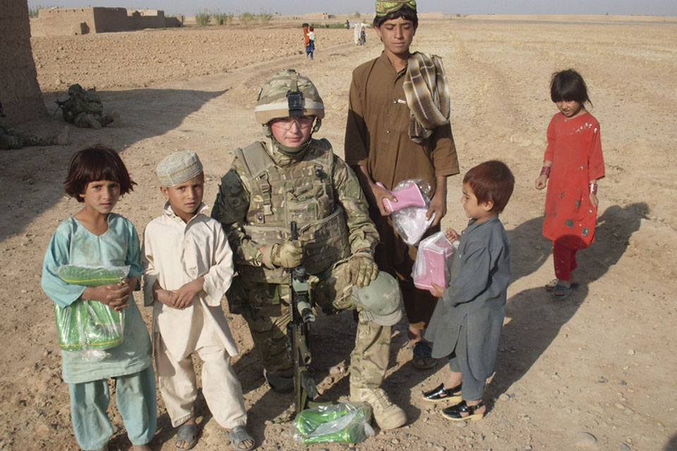 Private Marshall, A Company, 1st Battalion The Yorkshire Regiment, with Afghan children who have been given wellington boots for Eid