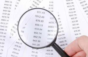 picture of financial figures viewed through magnifying glass
