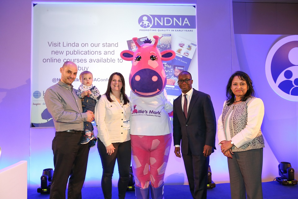 Mr and Mrs Thompson with son Leo, Millie the giraffe, Childcare Minister Sam Gyimah and National Day Nurseries Association Chief Executive Purnima Tanuku