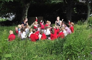 A class of children enjoy taking part in an outdoors learning session near their school