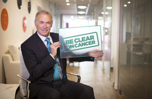 Dr Hilary Jones, Media Medic, holding the Be Clear on Cancer logo