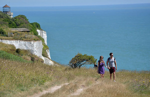 Two walkers stroll along a coastal path with white cliffs in the background