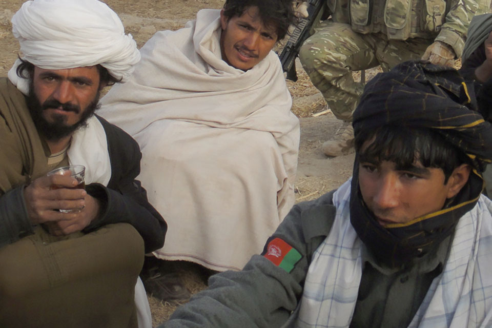 A member of the Afghan National Police with local residents at the shura in Noorzai
