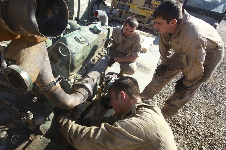 Craftsman Adam Evans (foreground) and Lance Corporal Craig Heaton (right) troubleshoot a Detroit Diesel V6 Logistics Vehicle System truck engine at the Intermediate Maintenance Activity lot in Camp Leatherneck