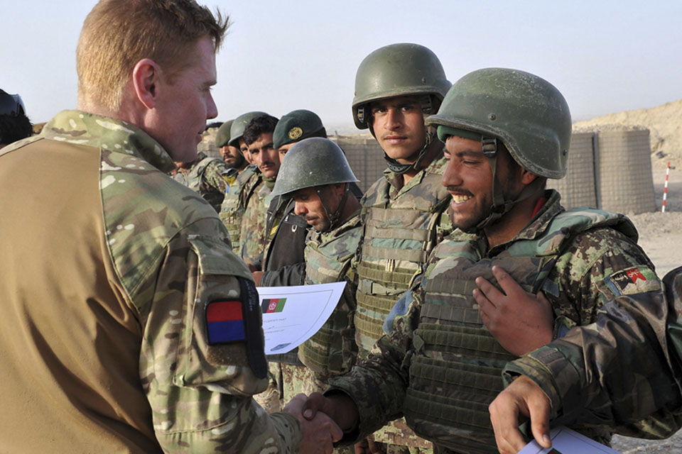 A British officer awards Afghan National Army Gunners with certificates on completion of their training