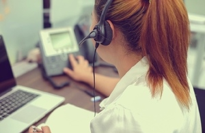 girl with headset on dialling telephone in an office