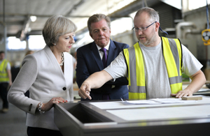 Prime Minister Theresa May speaking with Martek Designs Managing Director Derek Galloway and an employee.