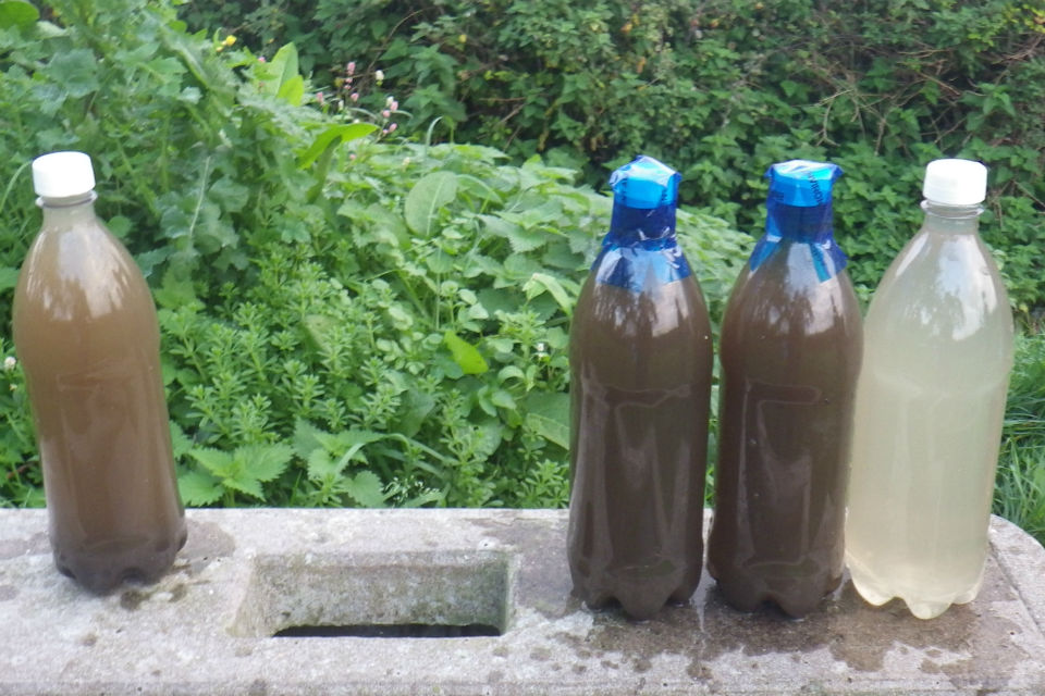 Bottles containing samples of water, ranging in colour from light brown, dark brown to clear