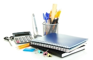 selection of office stationery including notepads, pens, calculator and bulldog clips