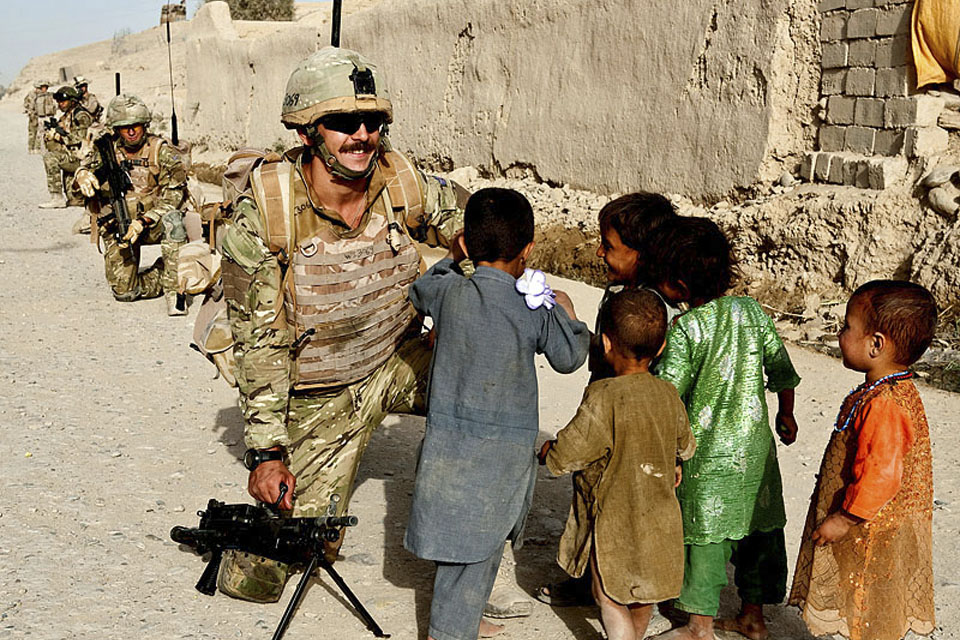 Royal Marines interact with Afghan children during a joint patrol with US Marines in Sangin