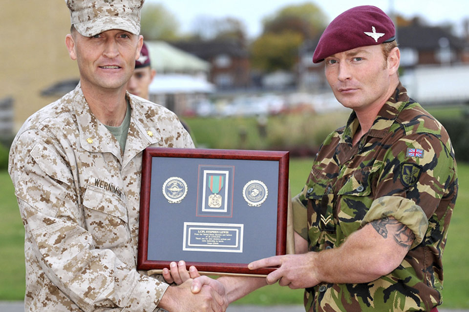 Major Timothy Wernimont, United States Marine Corps, presents Lance Corporal Stephen Lewis, 2nd Battalion The Parachute Regiment, with the (US) Navy and Marine Corps Achievement Medal