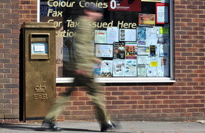A soldier walks past the gold-painted postbo