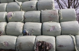Image shows waste dumped on land, wrapped in bales