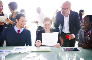 business colleagues reviewing paperwork with busy office background
