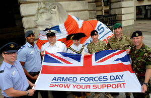 Armed Forces personnel with Armed Forces Day flag