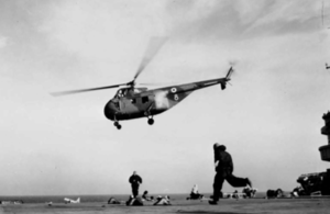 A Westland Whirlwind helicopter of the joint Royal Air Force/Army unit leaving HMS OCEAN with troops for Port Said.