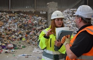Image shows Environment Agency officer speaking to waste site operator