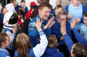 Tim Peake high-fives young people in the audience at Cardiff post-flight tour event.