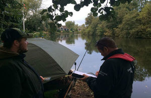 Environment Agency fisheries enforcement officer checks an angler's rod licence