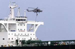 A Lynx helicopter hovers over a tanker