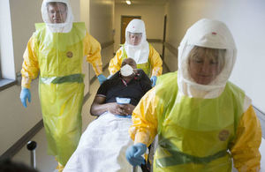 Medical personnel in protective clothing treating a patient