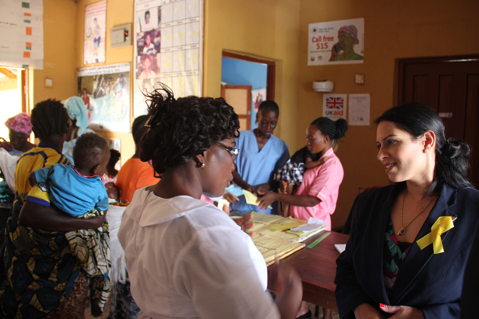 International Development Secretary Priti Patel talks with a midwife at the New Maforki clinic in Port Loko.