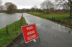 Photograph of a warning sign in front of a flooded country road.