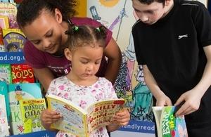 Three children looking at books