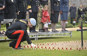 Prince Harry plants a cross for Lance Corporal of Horse Jonathan Woodgate at the opening of the Royal British Legion Wootton Bassett Field of Remembrance [Picture: Ben Birchall/PA Wire 2010]