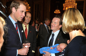 The Duke of Cambridge talks to Staff Sergeant Viv Vicary, of The Rifles, who holds his three-week-old son Hugo Eric Scott Vicary, and his wife Hanna during a reception to celebrate the Scott-Amundsen Centenary Race to the South Pole at Goldsmiths' Hall in