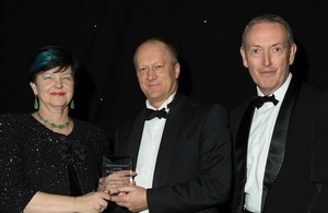 Baroness Neville-Rolfe presents the award to John Clarke with Lord Hutton in attendance