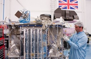 Engineer working on space technology in clean room.