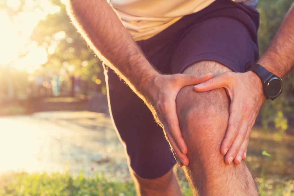 Stock picture of runner holding sore knee