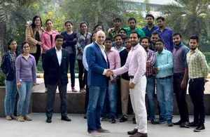 Gaist managing director Steve Birdsall shaking hands with Optimint's managing director, Deepak Dalal and his team.