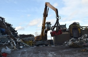 Image shows car being moved by a crane to the crusher
