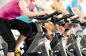 Gym goers on gym bicycles.