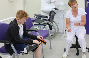 Child wearing new prosthesis talking to a doctor