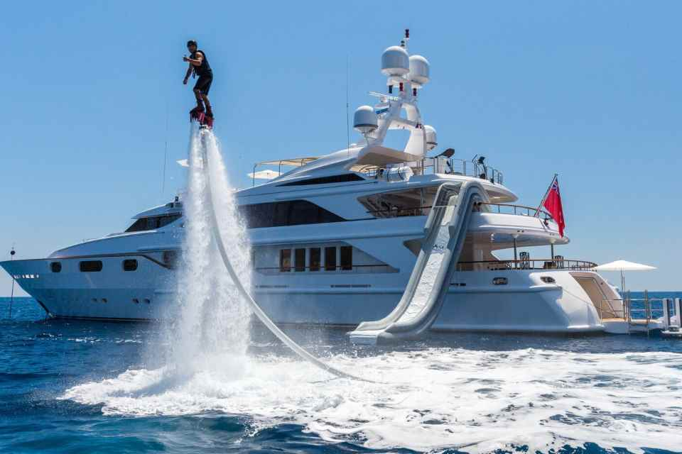 Man airborne on jet pack in front of superyacht with water slide.