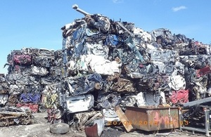Image shows a pile of scrap vehicles at a scrap yard.