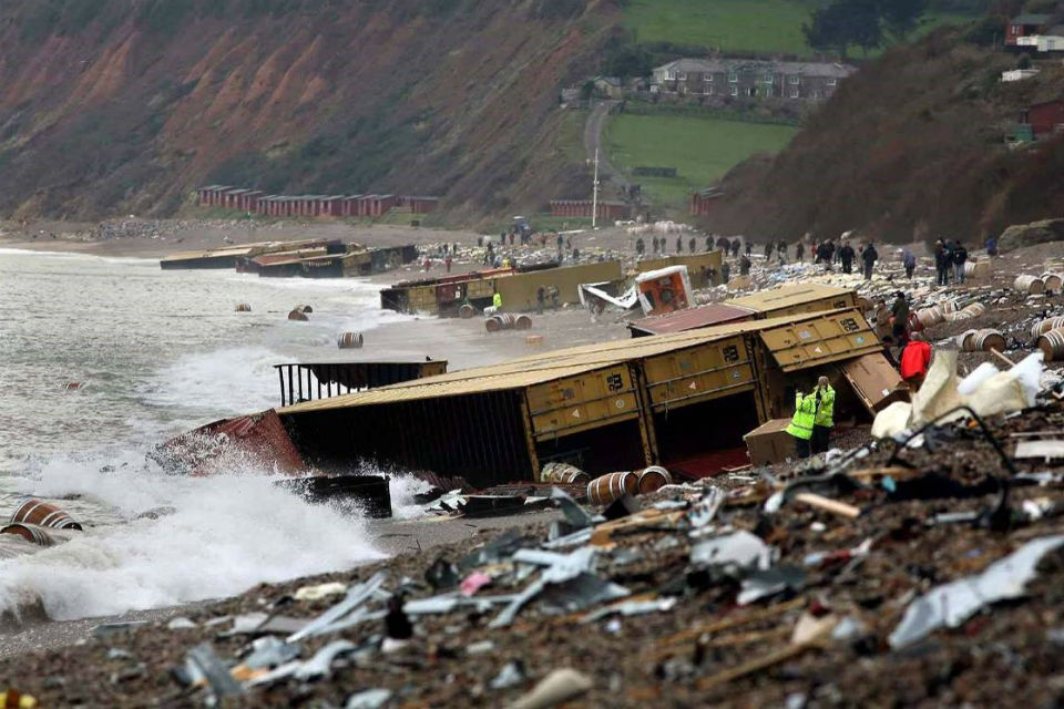 Crowds of people on shore among dozens of containers washed up