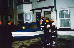 Firefighters rescue someone from their flooded house in water as high as their waists