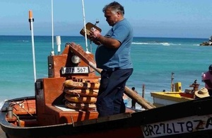 Image of man using mobile in small fishing boat.