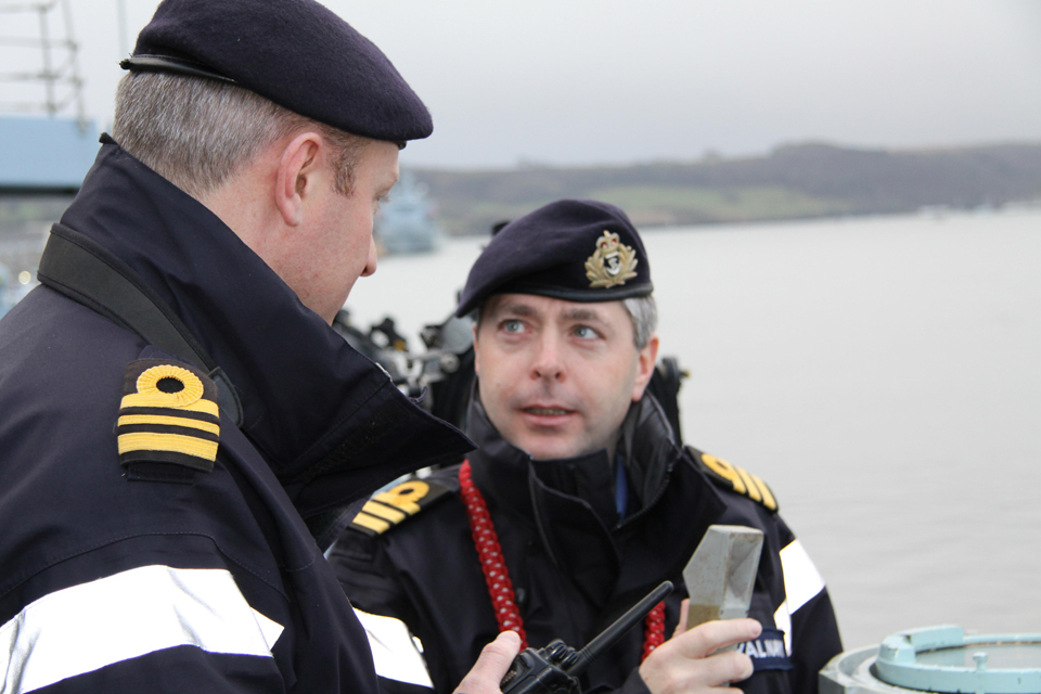 Commander Mike Smith speaks with a lieutenant commander on the ship's deck