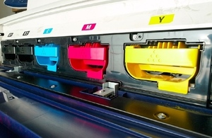 close up of CMYK ink boxes on digital printing press