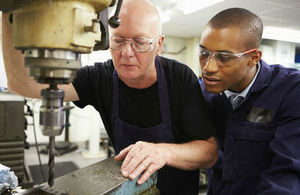 Engineering apprentice observing an older man operating machinery